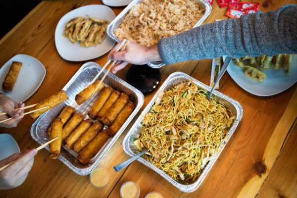trays of Asian noodles, egg rolls, and rice