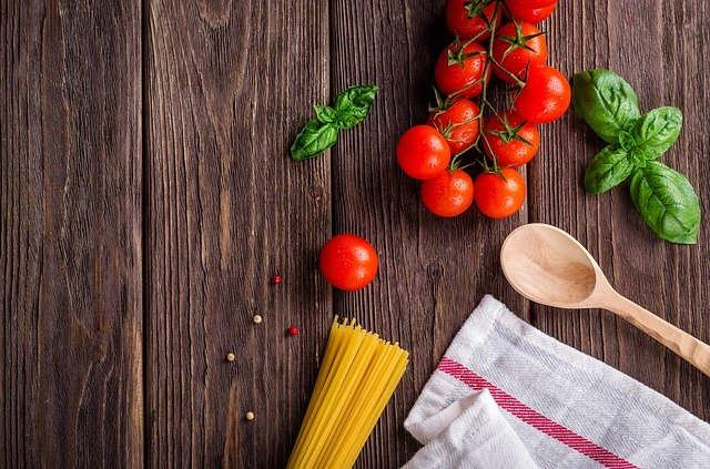 board with tomatoes, dry pasta, basil, towel, and wooden spoon