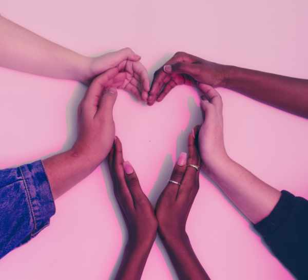 hands of people of different colors making heart shape
